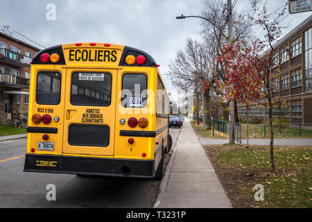 MONTREAL, CANADA - NOVEMBER 9, 2018: North American Yellow School Bus parked on a street, waiting for students with cars passing by with information i - Stock Image