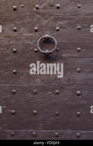 Old metal doorknocker on the brown painted wooden gate fixed with rivets in Bergamo, Lombardy, Italy. - Stock Image