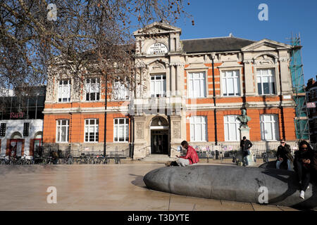 Person sitting reading outside the Tate Central Free Library building in Brixton South London SW2 England UK  KATHY DEWITT - Stock Image