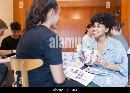 Smiling creative female designers discussing photograph proofs in office - Stock Image