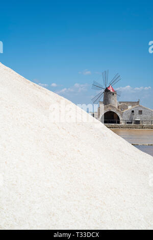 Mound of sea salt from salt pans at Saline di Trapani e Paceco and - behind - Museum of Salt and windmill at Nubia, Paceco, Sicily, Italy - Stock Image