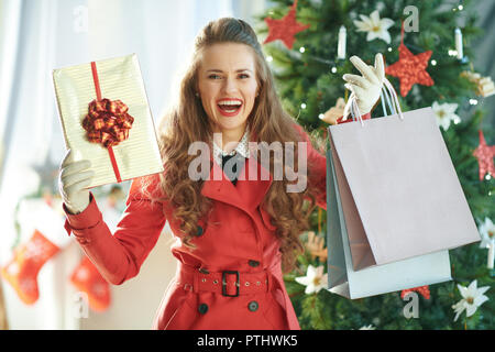 smiling young woman in red trench coat near Christmas tree showing shopping bags and Christmas present box - Stock Image