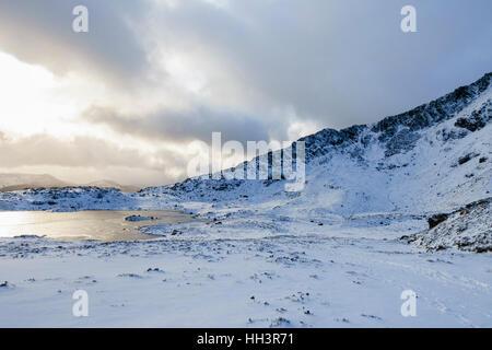Winter snow scene by Llyn y Foel lake below Moel Siabod Daear Ddu east ridge in Snowdonia National Park. Capel Curig, - Stock Image