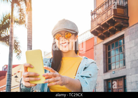 Happy Asian girl using mobile smartphone outdoor - Chinese social influencer having fun making video story for new trends social networks app - Stock Image