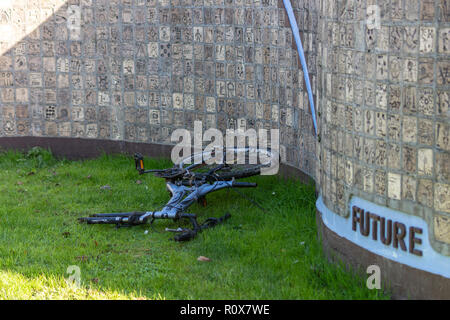 An abandoned bike missing its front wheel dumped in front of the 'Future' section of the millenium wall monument in Chippenham - Stock Image