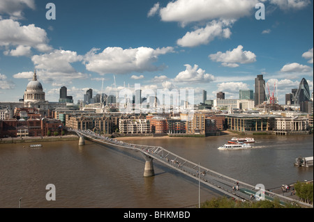photograph of millenium bridge over river thames with city of london skyline - Stock Image