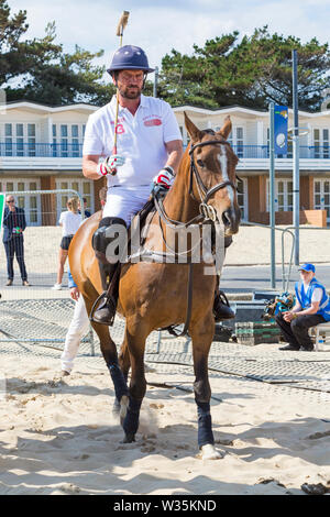 Sandbanks, Poole, Dorset, UK 12th July 2019. The Sandpolo British Beach Polo Championships gets underway at Sandbanks beach, Poole on a warm sunny day. The largest beach polo event in the world, the two day event takes place on Friday and Saturday, as visitors head to the beach to see the action. Nick Knowles, Rita Simons and Harry Redknapp attend for a penalty shoot out. Credit: Carolyn Jenkins/Alamy Live News - Stock Image