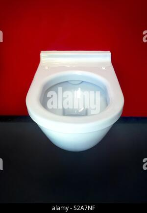 White ceramic toilet bowl on red background - Stock Image