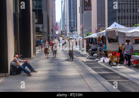 Man seated in the 6th Avenue sidewalk and a cyclist that was closing to car only for pedestrian with food stands in Manhattan, New York, USA - Stock Image