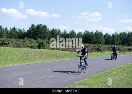 Motorcyclist and cyclist riding on a quiet road through Brantley veiw in the new forest national park. - Stock Image