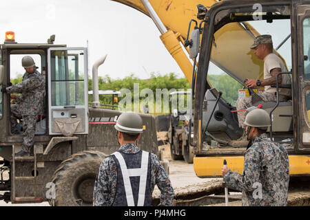 U.S. Air Force Airmen and members of the Japan Air Self-Defense Force participates in the Rapid Airfield Damage Recovery Bi-lateral Exercise Aug. 29, 2018, at Naha Air Base, Japan. Japanese and American service members participate in the exercise to foster relationships and exchange airfield repair techniques.(U.S. Air Force photo by Senior Airman Michael Jones) - Stock Image