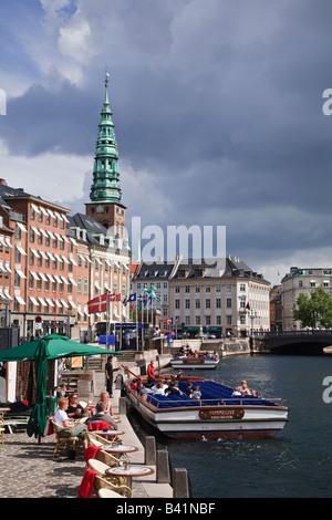 Canal tour boat and view towards Nikolaj Kirke from Gammel Strand, Copenhagen, Denmark - Stock Image