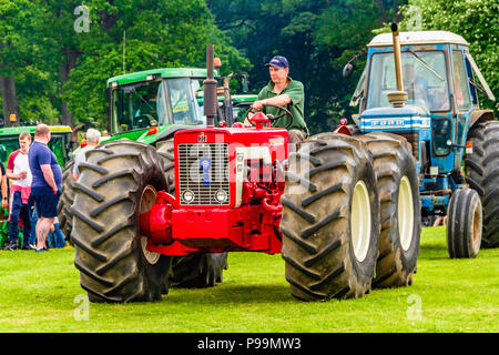 Man driving a prize-winning red tractor during a heritage tractor rally at Northumberland County Show, May 2018. - Stock Image