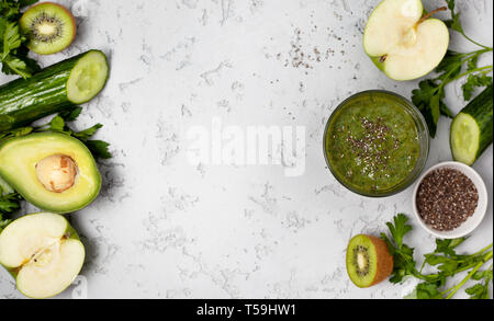 green smoothie in a glass, fresh fruits and vegetables on a gray background. view from above.  copy space - Stock Image