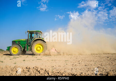 Badajoz, Spain - Oct 11th 2017: Farm tractor preparing dusty soil affected by drought. Drought and agriculture concept - Stock Image