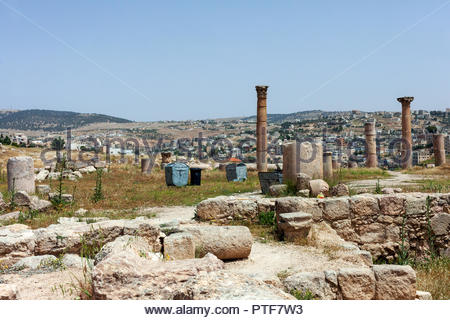 Rubbish Bins Among the Ancient Ruins of Jerash with Modern Jordan in the Background - Stock Image