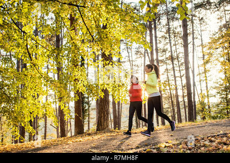 Two active female runners jogging outdoors in forest in autumn nature. - Stock Image