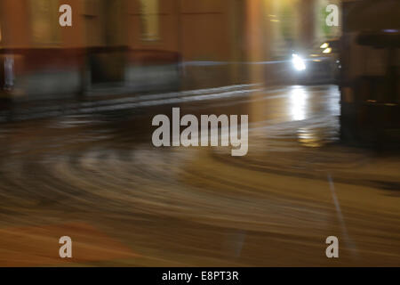 Car driving on an icy road reflected in a shop window. Swedish city on a winter night, blurred. - Stock Image
