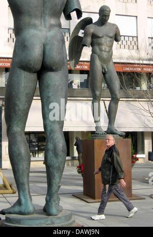 A man walks past the Icarus bronze sculptures by Polish artist  Igor Mitoraj at the Plaza Nueva in Sevilla, Spain, - Stock Image