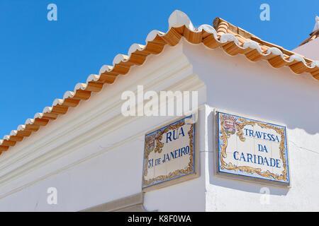 Two street name signs in ceramic tiles in a corner in Tavira, a town in Algarve, Portugal. - Stock Image