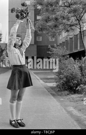 young schoolgirl member of the pioneer movement wearing her necktie and uniform while waving a bunch of flowers in the street 1970s hungary - Stock Image