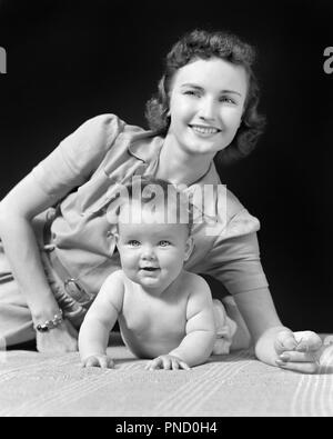1940s SMILING MOTHER AND BABY LYING ON ELBOWS LOOKING AT CAMERA - b8080 HAR001 HARS JOY LIFESTYLE FEMALES HEALTHINESS HOME LIFE HALF-LENGTH LADIES DAUGHTERS PERSONS CARING B&W EYE CONTACT HAPPINESS CHEERFUL PRIDE ON SMILES ELBOWS CONNECTION JOYFUL PERSONAL ATTACHMENT AFFECTION EMOTION JUVENILES MID-ADULT MID-ADULT WOMAN MOMS TOGETHERNESS BABY GIRL BLACK AND WHITE CAUCASIAN ETHNICITY HAR001 OLD FASHIONED - Stock Image