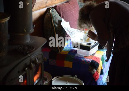 Checking germinating seeds indoors in February, using a woodburning stove  to maintain high temperatures, Wales, UK. - Stock Image