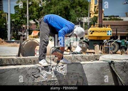 Thailand construction worker, builder drilling concrete wall - Stock Image