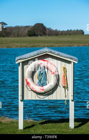 Lifebelt station at Holkham park lake, Norfolk, East Anglia, England, UK. - Stock Image