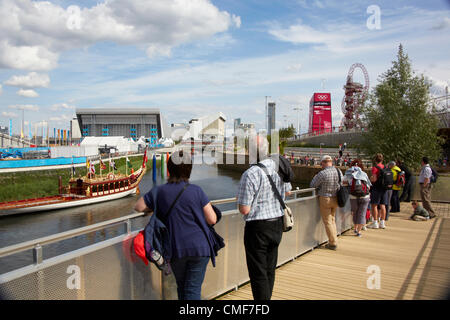 People by River Lea with Royal Barge, Arenas and Orbit at Olympic Park, London 2012 Olympic Games site, Stratford - Stock Image