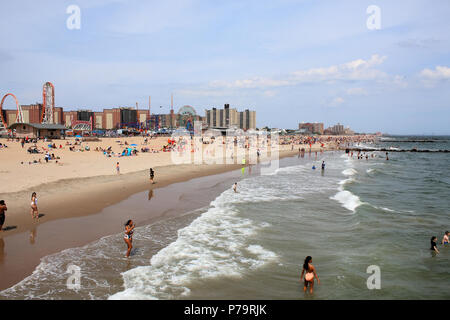 NEW YORK, NY - JUNE 29: People enjoying hot summer weather on Coney Island beach and boardwalk in Brooklyn on June 29th, 2017 in New York, USA. (Photo - Stock Image