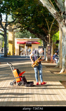 African American male busker playing the alto sax and tapping his foot in Alameda de Hercules in Seville - Stock Image