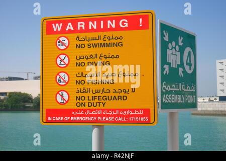 Bilingual warning signs, no swimming, no diving, no fishing, no lifeguard on duty, assembly point, Arabic and English, Bahrain Bay, Manama, Bahrain - Stock Image