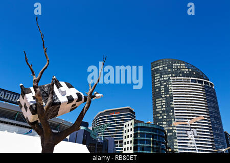 The Cow up a Tree sculpture in Melbourne Docklands.The Victoria Point Apartments,Medibank building,and Bendigo Bank can be seen in the background. - Stock Image