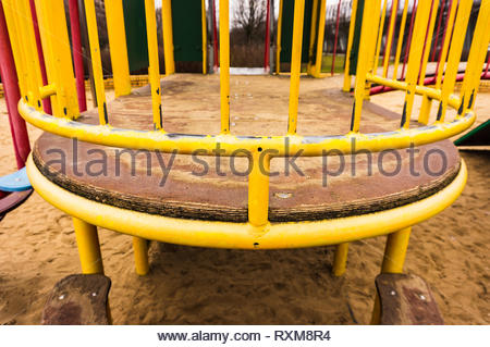 Close up of a metal yellow barrier of a climb equipment at a playground. - Stock Image