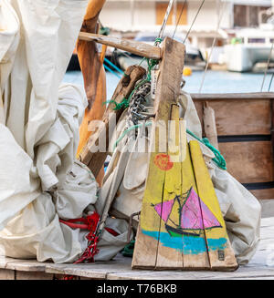 a colorful depiction of a sail boat painted on scrap wood in Gustavia, St Barts - Stock Image