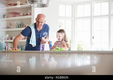 Father and daughter having fun while cleaning the kitchen - Stock Image