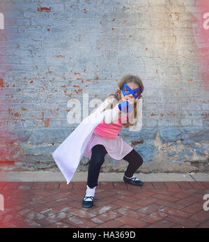A little super hero child is standing outside against an old vintage brick wall for an education or creative concept. - Stock Image