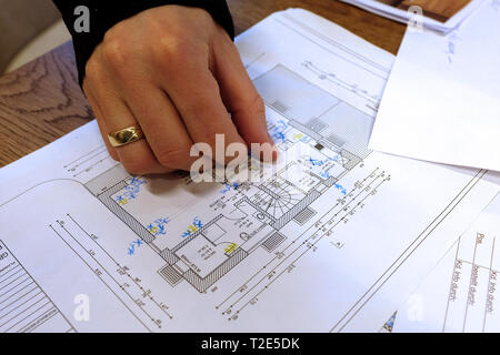 Architect, engineer discussing blueprint of a house with its clients in the office - Stock Image