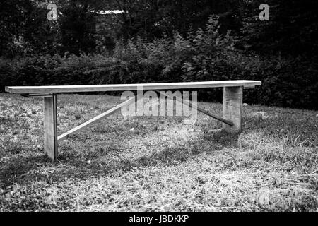 A wooden bench on a meadow. Black and white - Stock Image