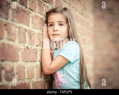 Girl, 5 years old, leaning against a wall, portrait, Germany - Stock Image