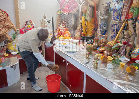 An older Hindu worshipper breaks a coconut shell, symbolic of breaking the ego to attain spiritual & personal development. In Jamaica, Queens, NYC. - Stock Image