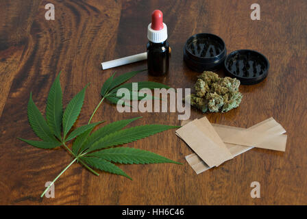 Cannabis sativa weed leafs and flower buds on wooden background with grinder and large smoking paper - Stock Image