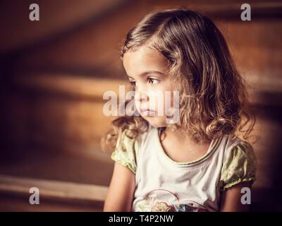 Girl, 3 years, sitting on the stairs, melancholic gaze, Portrait, Germany - Stock Image