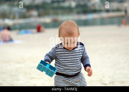 Adorable Baby Boy Playing With Sand And Blue Plastic Shovel On The Sea Beach - Stock Image