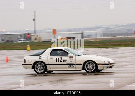 A 1987 White Mazda RX-7 Turbo in an autocross race at a regional Sports Car Club of America (SCCA) event - Stock Image