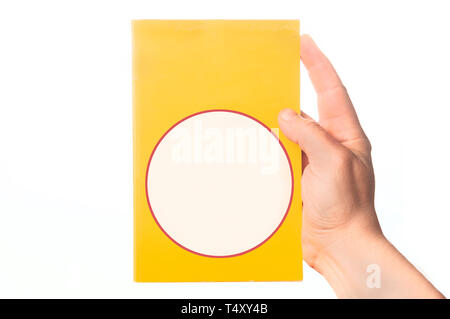 Man hand holding a crime novel book with blank cover on white background - Stock Image