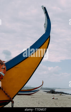 Typical colourful Moliceiro fishing boats on the beach in Espinho, Portugal. - Stock Image