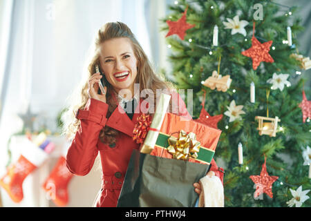 smiling stylish woman in red trench coat with shopping bag full of Christmas present boxes talking on a smartphone near Christmas tree - Stock Image