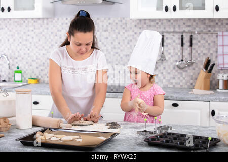 Girl Wearing Chef Hat Helping Her Mother To Make Cookies At Kitchen - Stock Image